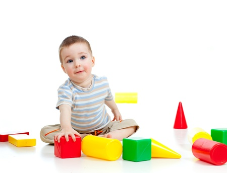 developmental: smiling child playing with colorful building blocks or bricks Stock Photo