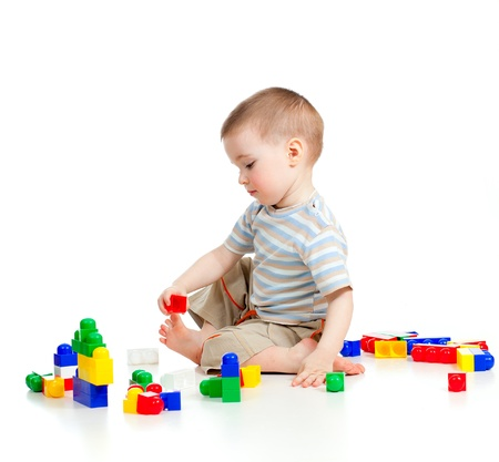 cheerful child boy playing with construction set over white background photo