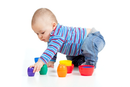 baby playing with colurful cup toys on floor, isolated over white photo