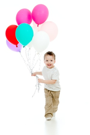 niño corriendo: Niño alegre niño divertido con un montón de globos de colores en la mano aislado en blanco