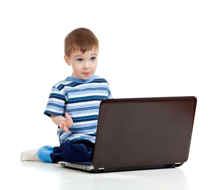 Cheerful child boy using a laptop over white background photo