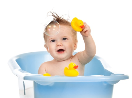 charming baby having bath in blue tub and playing with soap bubble photo