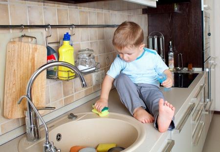 adorable little boy washing sink on kitchen photo