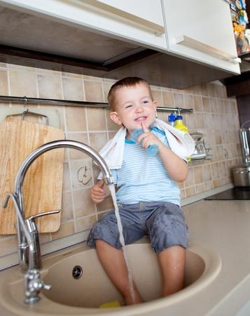 funny little child boy washing dish on kitchen photo