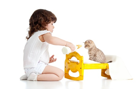 curly child girl playing with kitten as mother with baby photo