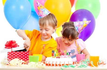 adorable children celebrating birthday party and opening gift box photo