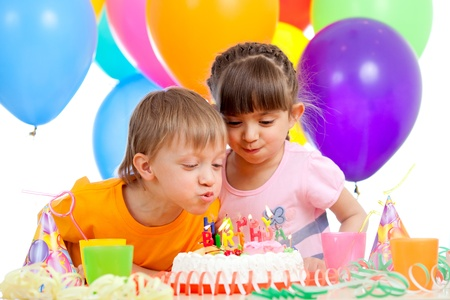 cake with candles: kids celebrating birthday party and blowing candles on cake