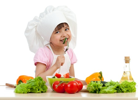 kids food: Chef girl preparing and tasting healthy food over white background