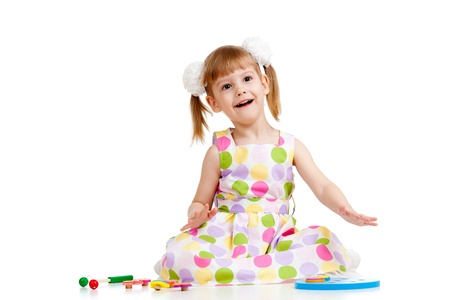 Funny little girl playing with toys, isolated over white photo