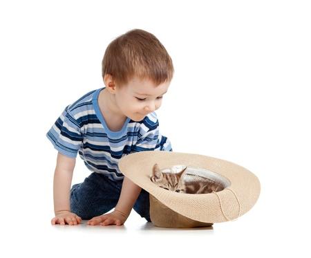niño jugando con el gato en el sombrero Foto de archivo