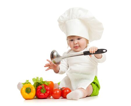 Kid in chef hat with healthy food vegetables photo