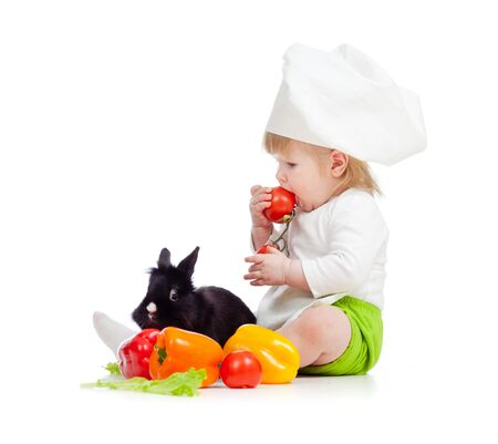 Kid in chef hat with healthy food and rabbit photo