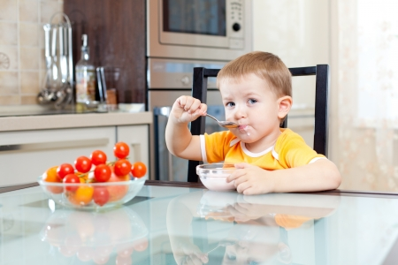 kid eating at home in kitchen photo