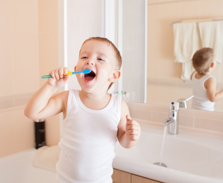 Boy cleaning teeth in bathroom photo