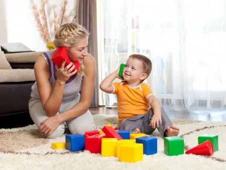 ni�os ayudando: chico lindo madre y el hijo juegan juntos en interiores Foto de archivo