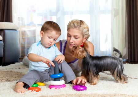 yorky: perro de la madre, el ni�o chico y una mascota de juguete jugando juntos en interiores Foto de archivo