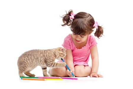 Cute kid drawing with pencils  Kitten next to girl  photo