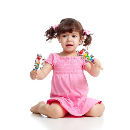 Child girl playing with musical toys  Isolated on white background photo