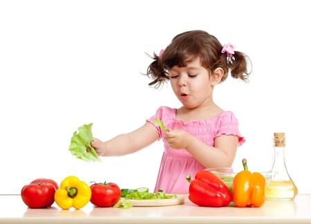 kids eating healthy: cute girl preparing healthy food vegetable salad