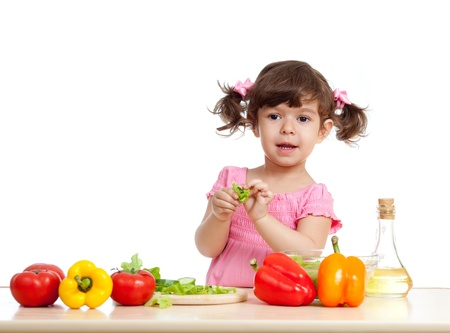 little girl making vegetable salad photo