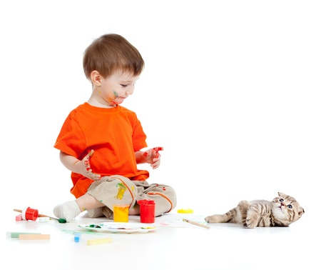 Adorable niño sucio con las pinturas buscando al gato