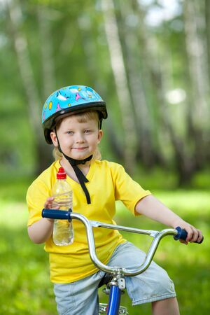 safe drinking water: Cute kid on bicycle  Child holding bottle with water