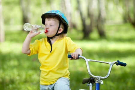 safe drinking water: Cute child kid on bicycle and drinking  water fom bottle Stock Photo