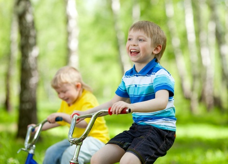 niños en bicicleta: adorables niños montados en sus bicicletas en el parque