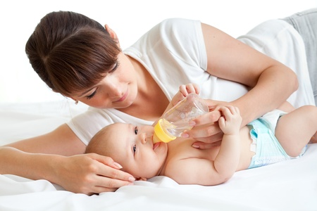 teteros: joven madre alimentando a su beb� adorable Foto de archivo