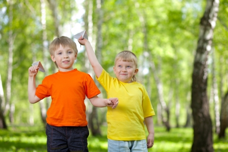 Children playing and flying a paper airplane photo