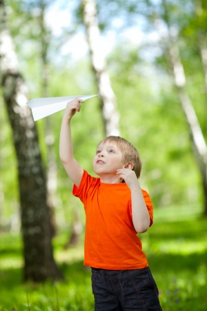 Cute boy holding a paper airplane in park photo