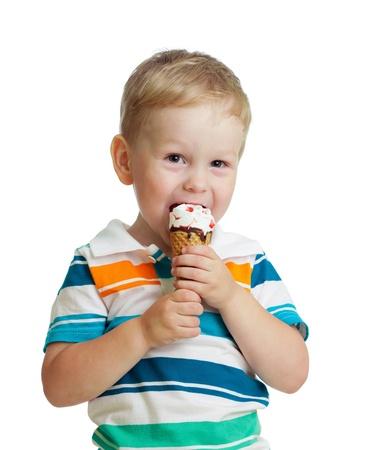 eating ice cream: happy kid boy eating ice cream in studio isolated Stock Photo