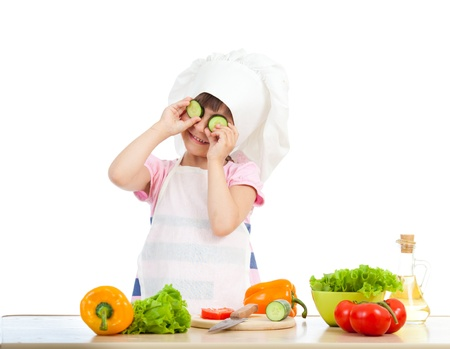 child food: Funny chef girl preparing healthy food over white background