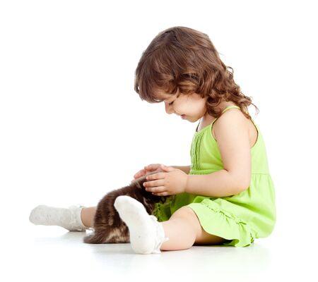 Little kid girl strokes kitten  Isolated on white background photo