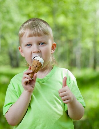 kids having fun: kid eating a tasty ice cream outdoor and showing thumb up Stock Photo