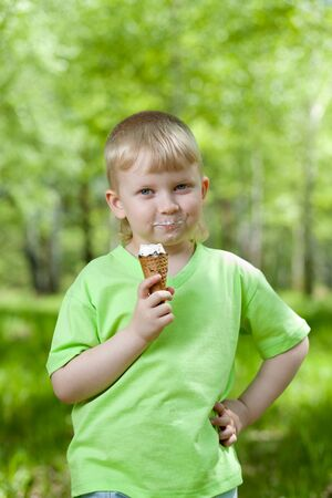 happy kid eating a tasty ice cream outdoors photo