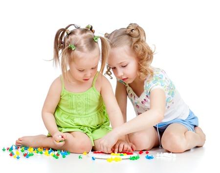 ni�os ayudando: dos hijos hermanas paly juntos, aislados sobre fondo blanco Foto de archivo