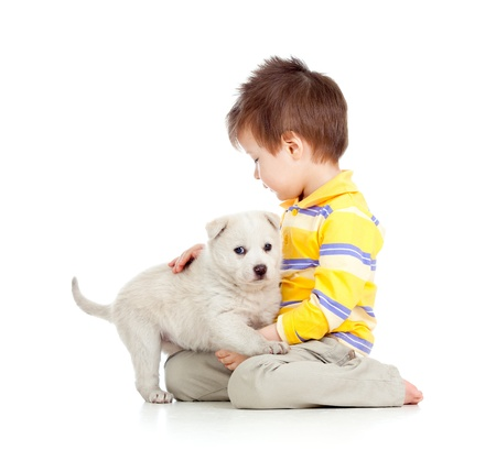 two boys: kid hugging puppy on white background