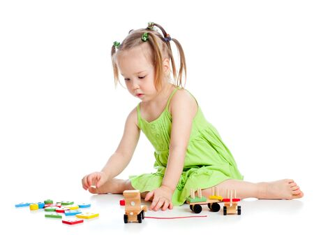 little kid girl playing with colourful toys, isolated over white photo