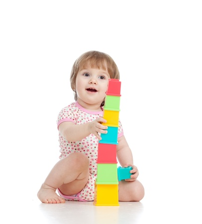 Funny little kid playing with cup toys, isolated over white photo
