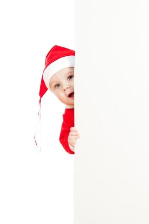 baby kerst: kleine Kerstman kind op zoek van achter het plakkaat Stockfoto