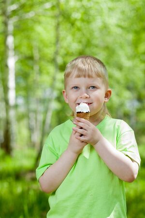 child ice cream: young boy eating a tasty ice cream outdoors Stock Photo