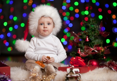 funny baby in Santa Claus hat on bright festive background photo
