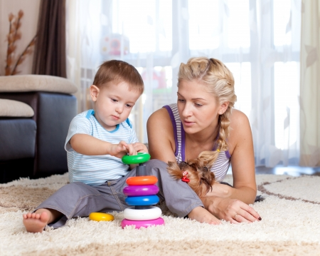 keen: cute mother and kid boy playing together indoor Stock Photo