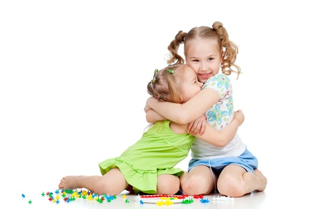 sisters girls playing and embracing over white background photo