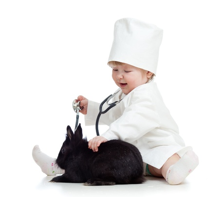 Adorable kid with clothes of doctor  Girl is playing with pet bunny Stock Photo - 14652184