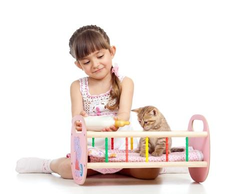 child girl feeding and playing kitten cat photo