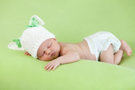Funny sleeping newborn baby  Bunny cap on head of girl  photo