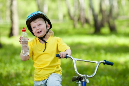 Cute kid on bicycle  Child holding bottle with water  photo