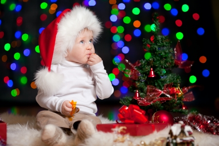 christmas funny baby in Santa Claus hat on bright festive background photo